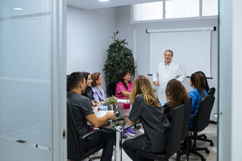 A senior orthodontist lecturing to orthodontic students at university.