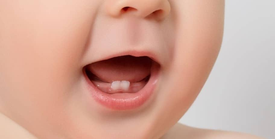 Baby showing two front teeth.